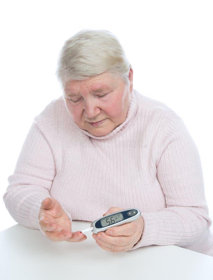Diabetes senior woman measuring glucose level blood test royalty free stock photo