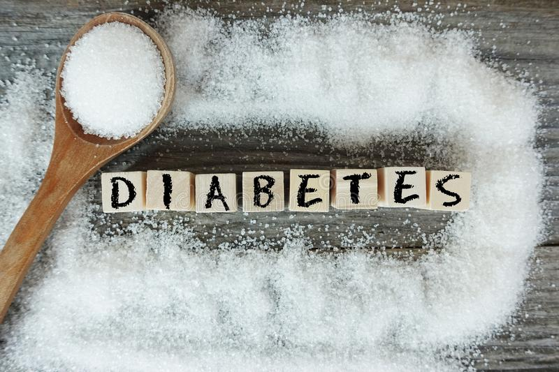 Diabetes word on wooden letters with crystalized white sugar as frame stock images