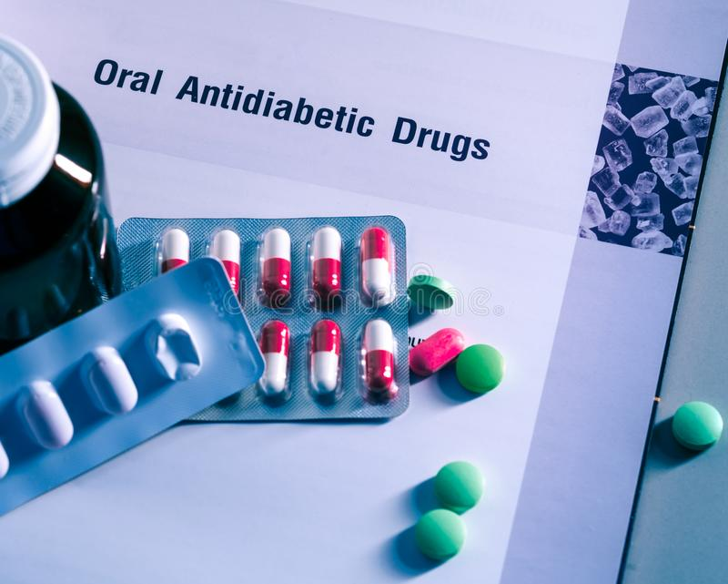 Diabetesdrogen in den Sätzen und und Medizinflasche gesetzt auf Lehrbuch Grüne Tabletten und rosa-weiße Kapselpillen Diabetes mel lizenzfreies stockbild