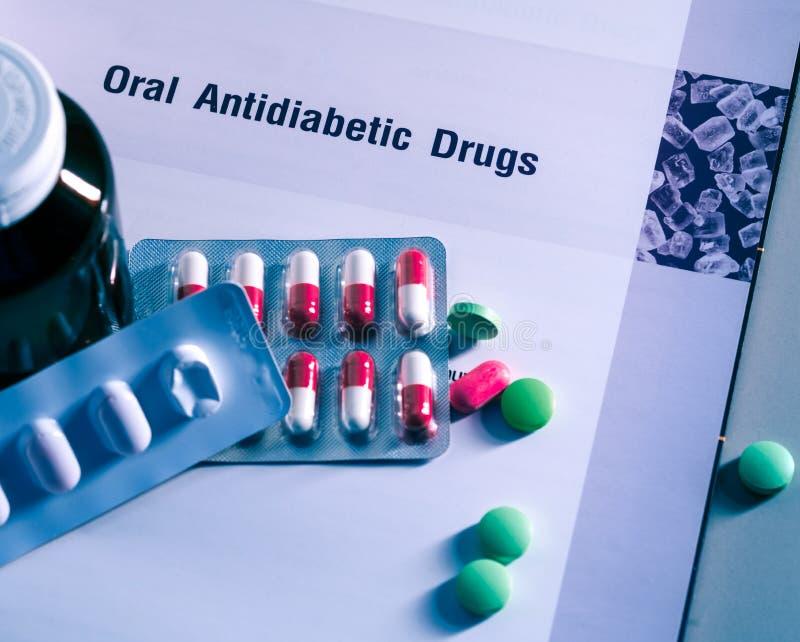 Diabetesdrugs in pakken en en geneeskundefles op handboek wordt geplaatst dat Groene tabletten en roze-witte capsulepillen Mellit royalty-vrije stock afbeelding