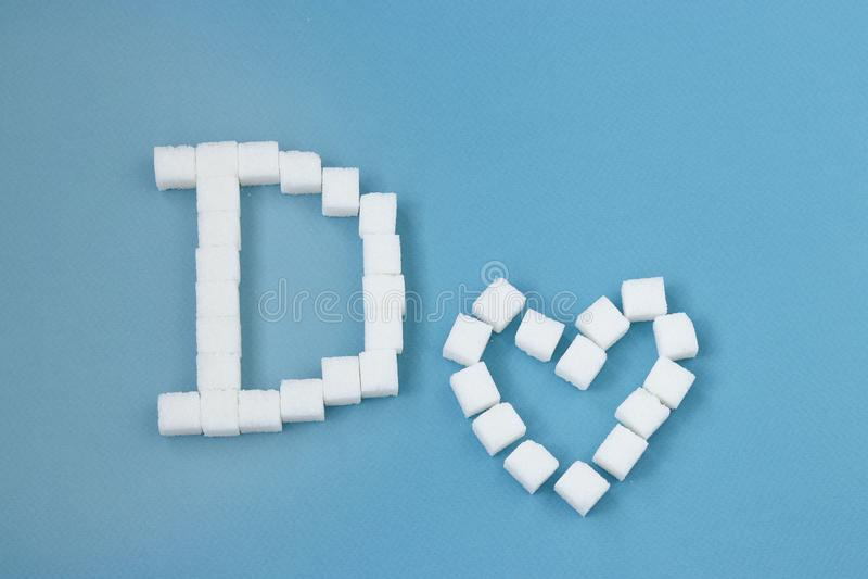 Diabeteskonzept: ein großer Buchstabe D und ein Herz gemacht von den Zuckerwürfeln auf blauem Hintergrund stockbild
