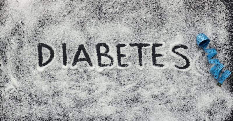 Diabeteswort geschrieben auf weißen zerstreuten Zucker stockbild