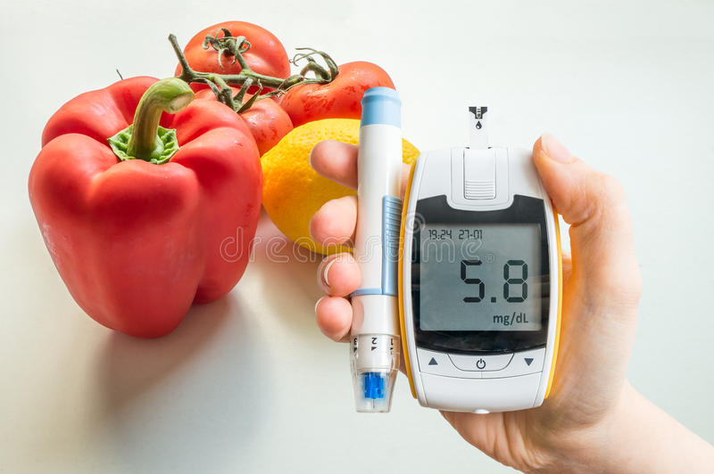Diabetic diet, diabetes and healthy eating concept. Glucometer and vegetables. stock images