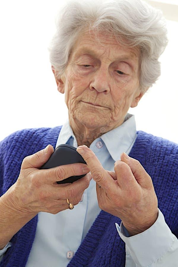 Diabetic old woman measuring her sugar level. Senior woman checking sugar level royalty free stock photos