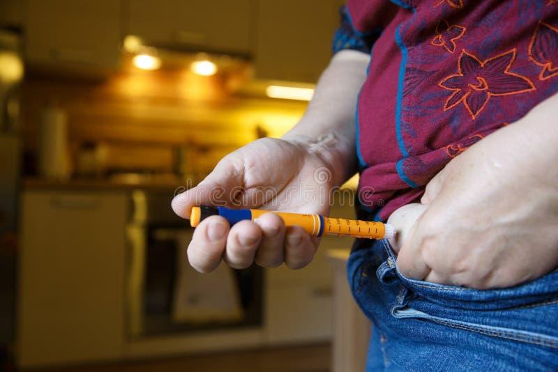 Diabetisk patient som injicerar sig med insulinskottet arkivfoto