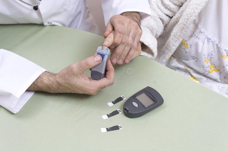 Diabetologist punctures the finger of a woman suffering from diabetes. stock photo