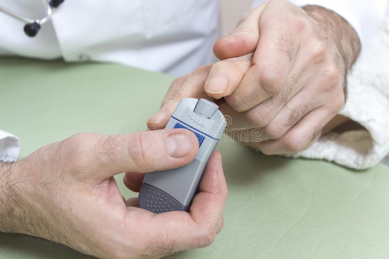 Diabetologist punctures the finger of a woman suffering from diabetes. royalty free stock photography