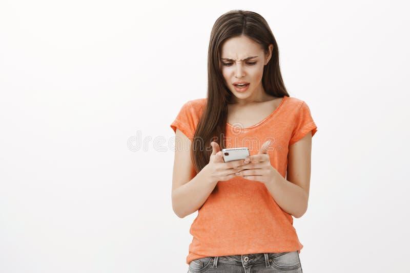 Diable vous moyen nous dissolution Portrait de femme européenne ordinaire confuse frustrante dans le T-shirt orange, se tenant photo libre de droits