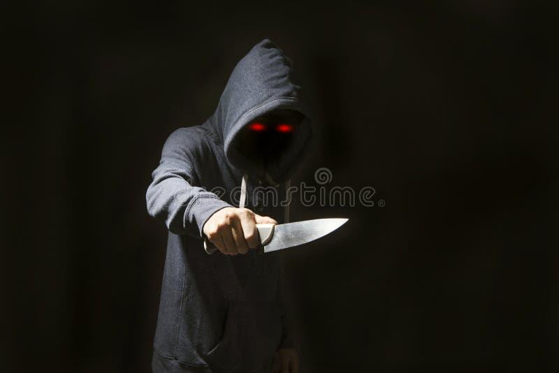 Diablo misterioso del hombre encapuchado y cuchillo para el robo en oscuridad imagen de archivo libre de regalías
