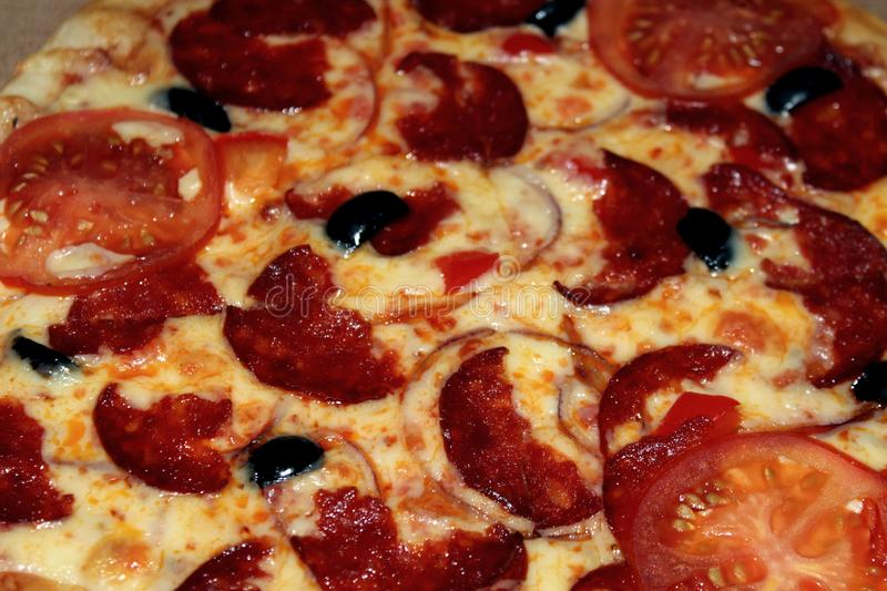 Diablo pizza with olives, smoked sausage stock photography