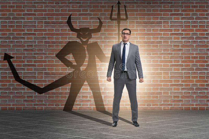 Diablo que oculta en el hombre de negocios - concepto del alter ego imagenes de archivo