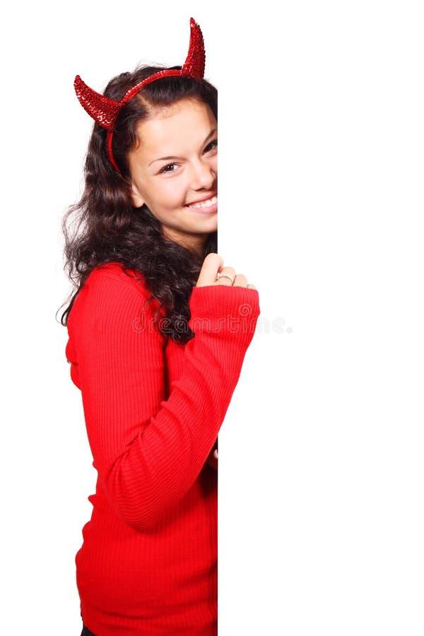 Diablo sonriente detrás de la tarjeta blanca fotos de archivo