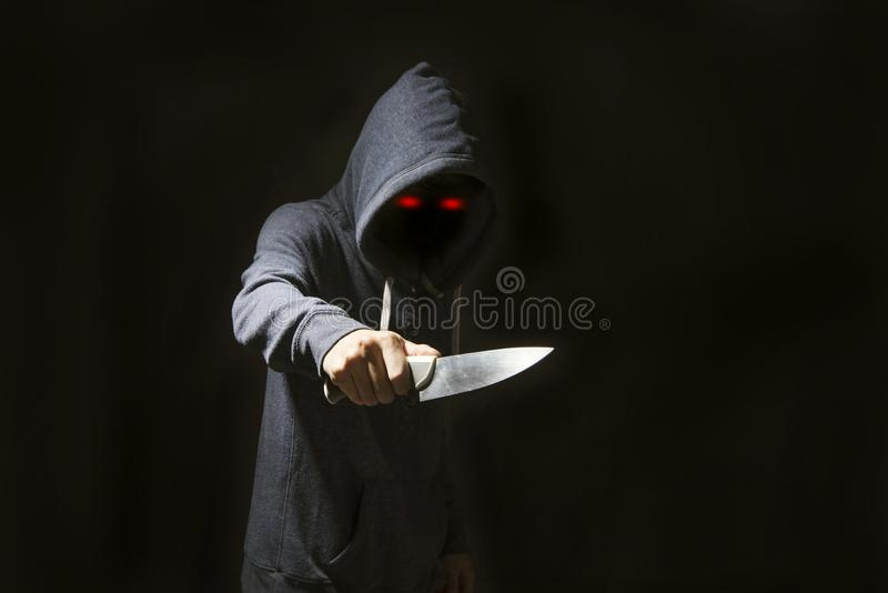 Diabo misterioso do homem encapuçado e faca para a extorsão na obscuridade imagem de stock royalty free