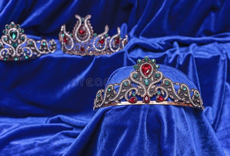 Diadem with green stones on a blue velvet background. Eastern tiara. Jewelry design stock photos