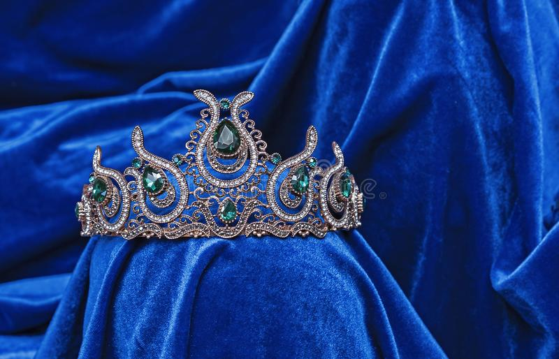Diadem with green stones on a blue velvet background. Eastern tiara. Jewelry design royalty free stock photo