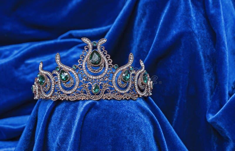 Diadema com pedras verdes em um fundo azul de veludo Tiara oriental Projeto da joia foto de stock royalty free