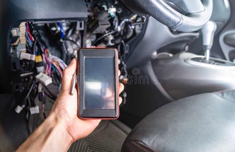 Diagnóstico de falhas do carro: um auto varredor portátil com relação OBD2 na mão do ` s do eletricista No fundo do fotos de stock royalty free