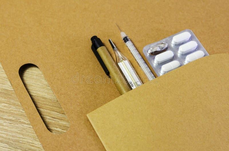Diagnóstico médico ou modelo da prescrição do doutor Seringa, bloco de notas da página vazia, atadura, tabuletas, termômetro e am foto de stock