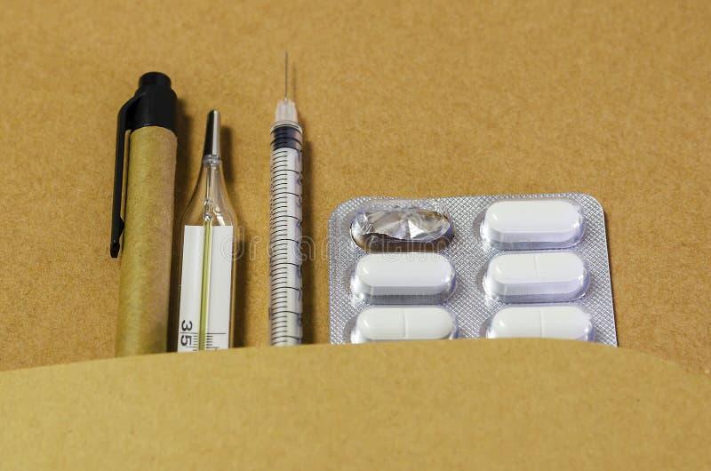 Diagnóstico médico ou modelo da prescrição do doutor Seringa, bloco de notas da página vazia, atadura, tabuletas, termômetro e am fotografia de stock