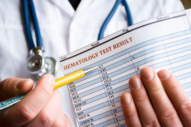 Diagnóstico na hematologia e na foto hematológica do conceito das análises de sangue O doutor realiza em seu resultado da mão da  imagens de stock royalty free