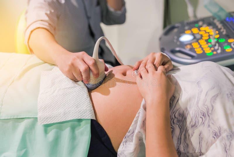 Diagnósticos del obstétrico que examinan a la mujer embarazada con el equipo de la exploración del ultrasonido imagen de archivo