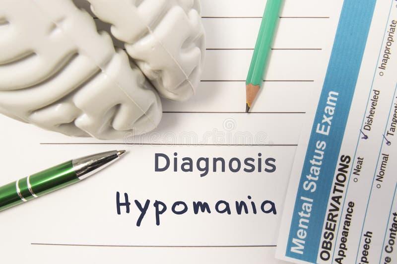Diagnose Hypomania Het cijfer van menselijke hersenen, het resultaat van geestelijk statusexamen, de pen en het potlood omringden stock fotografie