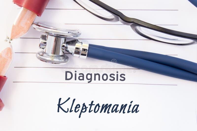 Diagnosekleptomanie De psychiatrische diagnosekleptomanie wordt geschreven op document, waarop stethoscoop en zandloper voor het  stock fotografie