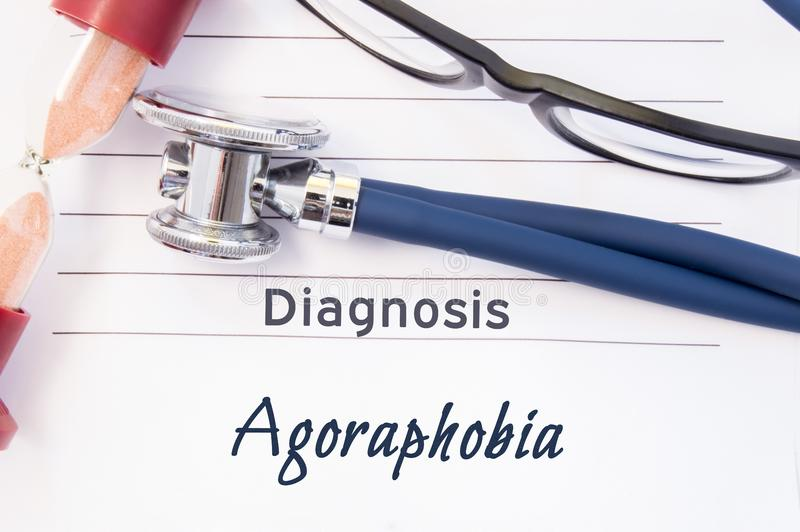 Diagnosis Agoraphobia. Psychiatric diagnosis Agoraphobia is written on paper, on which lay stethoscope and hourglass for measuring. Time to research. Concept stock photos