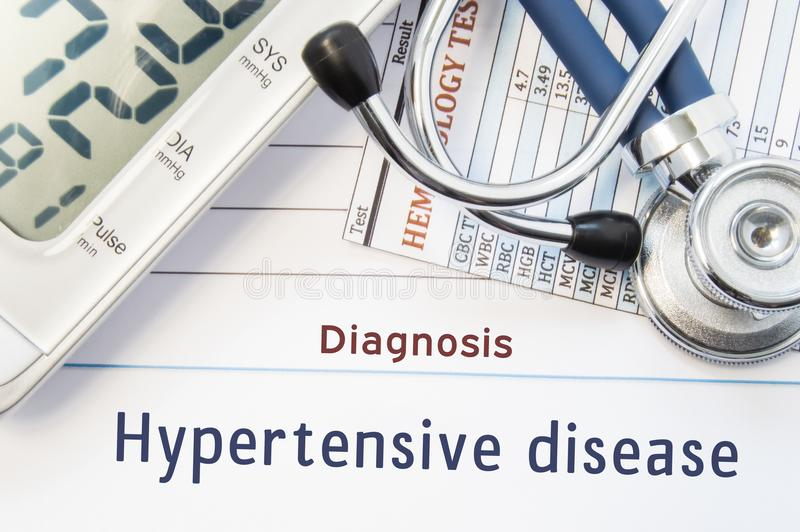 Diagnosis Hypertensive disease. Stethoscope, hematology blood test result and digital tonometer lie on sheet of paper with printed. Title diagnosis of vascular stock photos