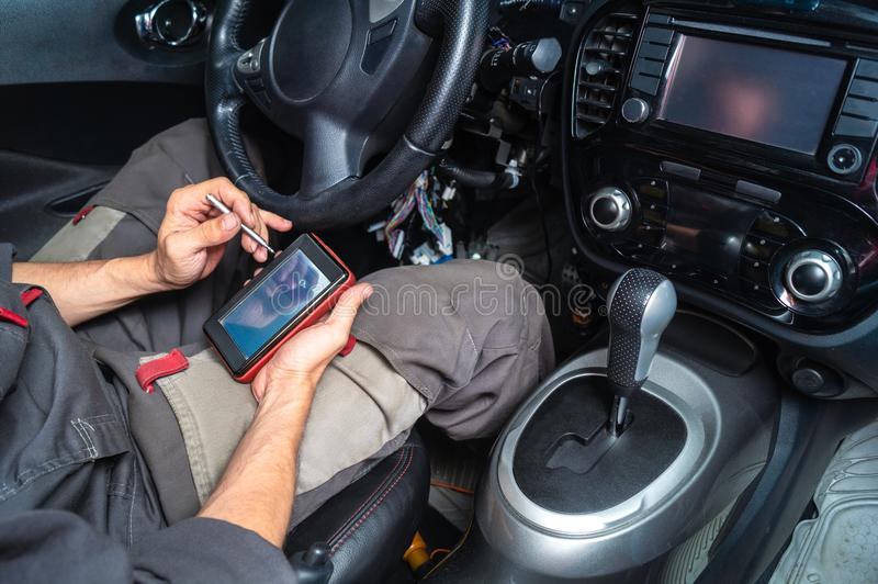 Diagnostics Of Car Failures: An Electrician In Gray Clothes Is ...