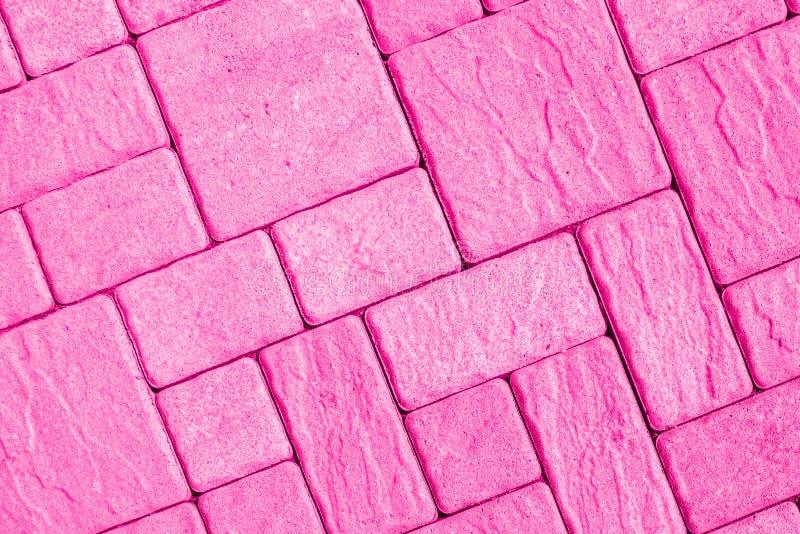 Diagonaal bestratingspatroon dat in helder roze wordt gestemd stock fotografie