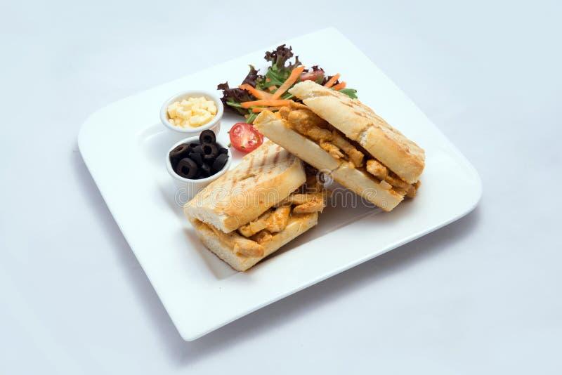 Diagonaal Heldenschot van een ontbijtschotel met de geroosterde sandwich van kippenpanini met olijven, kaas & groentenwortel, stock foto's