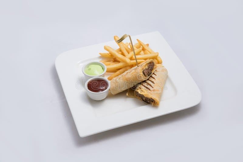 Diagonaal Heldenschot van een sandwich van de rundvleesomslag met samoeraien & alger saus en gebraden gerechten aan de kant, op e stock foto