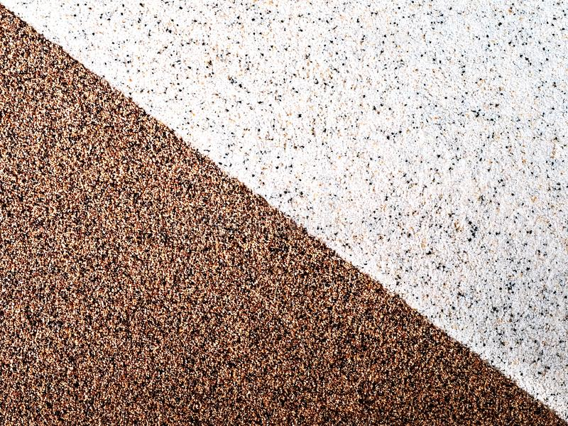 Diagonal, background of two triangles, with brown and light pebbles, grains. Abstract bright background with dots stock image