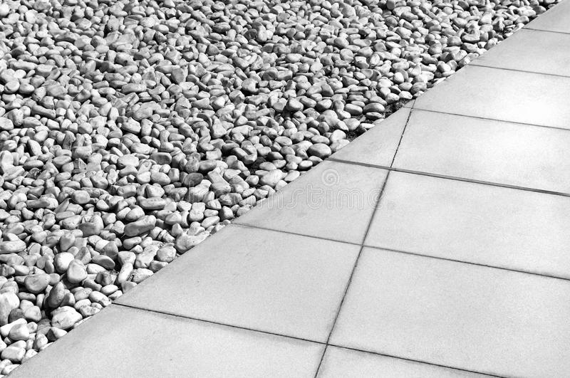 Diagonal dividing line between gray tiles and white gravel stock photography
