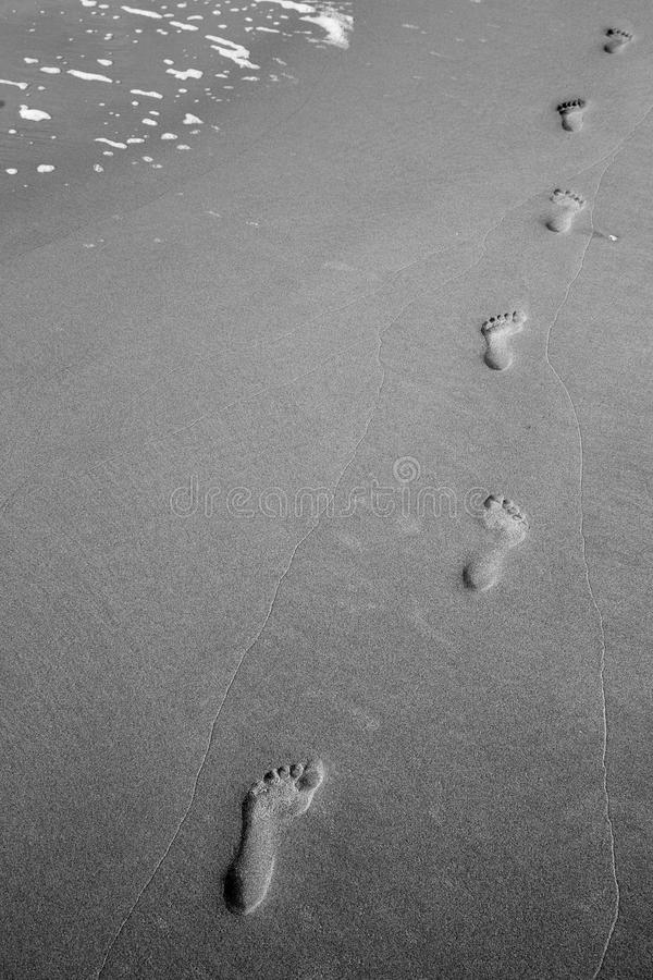 Diagonal Footprints in the Sand. Solitary footprints on a sandy beach leading towards the horizon