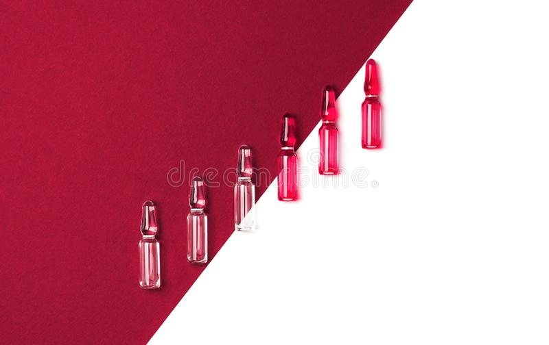 Diagonal line of ampules for injections with red and transparent liquid on isolated white and dark red background stock photo