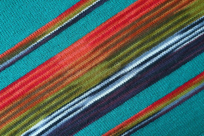 Diagonal Patterns and the Texture of Turquoise Blue with Red and Green Striped Alpaca Knitted Wool Fabric royalty free stock images