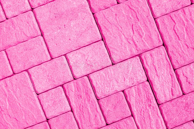 Diagonal pavement pattern toned in bright pink. Highly detailed street pavement background with diagonal geometric pattern made of various square blocks with stock photography
