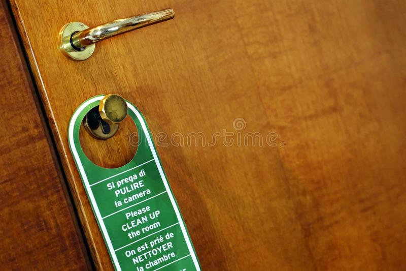 Clean up the room, door. Diagonal photo of a typical hotel door sign: green sign at red wooden background, golden handle. If the guest needs a cleaning service royalty free stock image