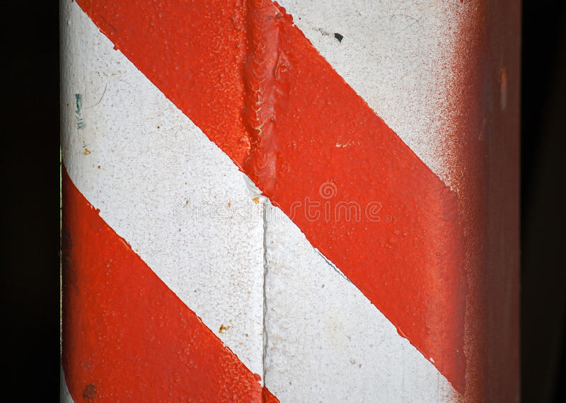DIAGONAL RED AND WHITE BANDS ON A PILLAR. Red and white painted bands on a metal pillar royalty free stock photos