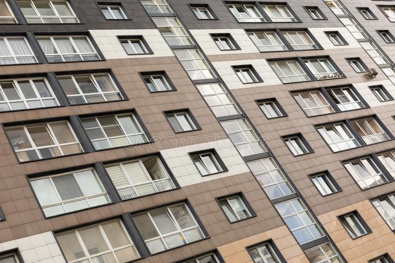 Diagonal view of modern new apartment building facade with gray and white, beige parget walls. Exterior design. Diagonal view of modern new apartment building stock photography