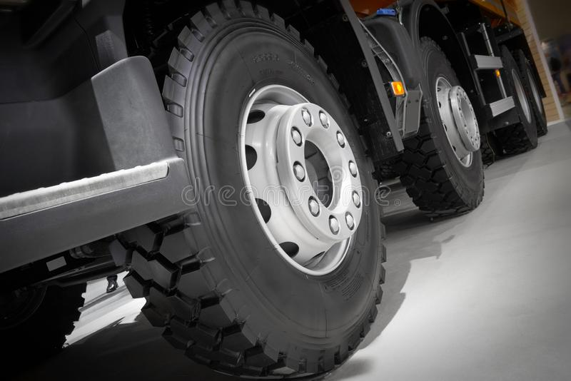 Diagonal view on tipper truck wheels and tires with blured background. Truck wheel rim. Truck chassis exhibit on car Exhibition. C. Ommercial transport with royalty free stock photo