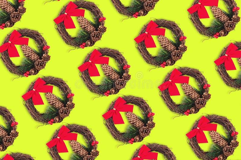 Diagonala rader av julkransar med kotten och att fatta av julträdet och röda filialer för pilbåge för textil torra och på guling royaltyfri foto