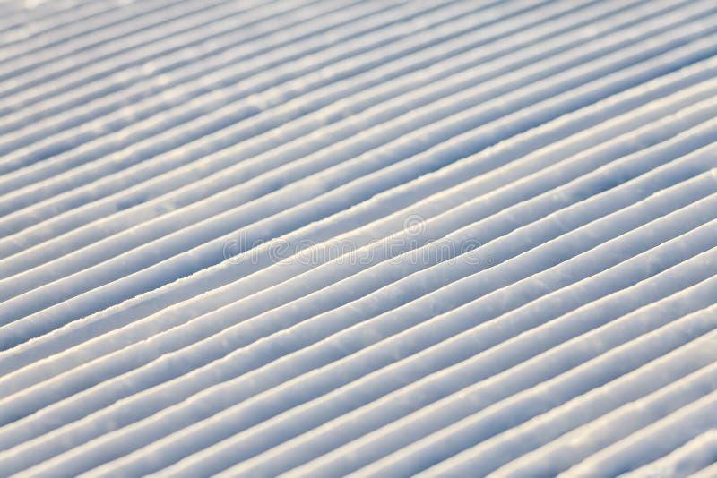 Diagonala snowcatspårlinjer på en skidalutning texturerar bakgrund royaltyfri bild