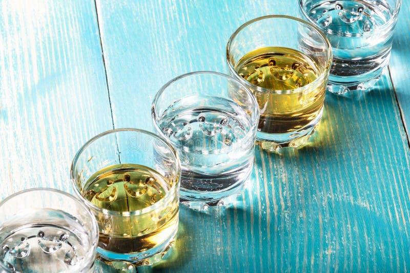 Diagonale des verres avec la boisson alcoolisée de différentes couleurs image stock