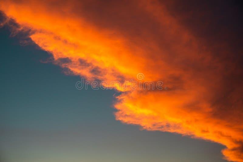 Diagonale oranje stormachtige wolk in zonsonderganglicht bij blauwe hemelachtergrond als abstract aardbehang royalty-vrije stock fotografie