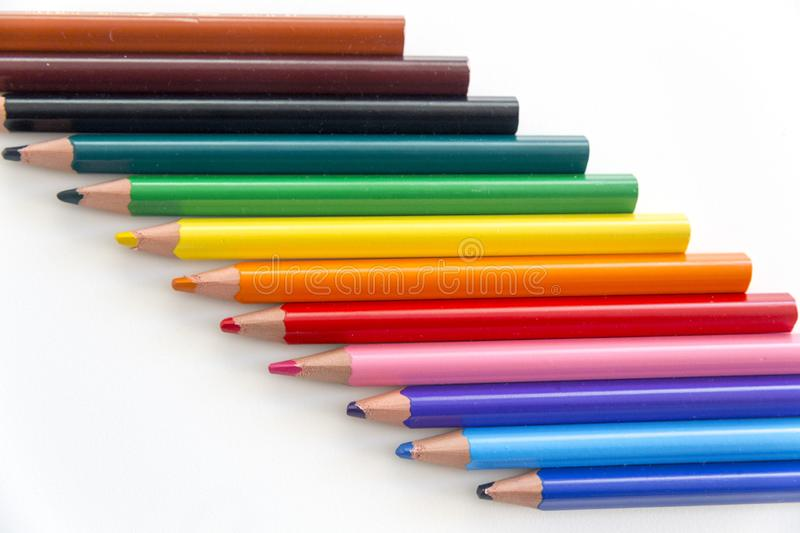 Diagonally arranged set of colorful crayons on neutral background. royalty free stock image