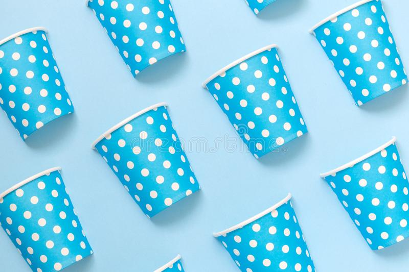 Diagonally positioned paper cups isolated on blue background. Minimalistic fashionable concept. stock photos