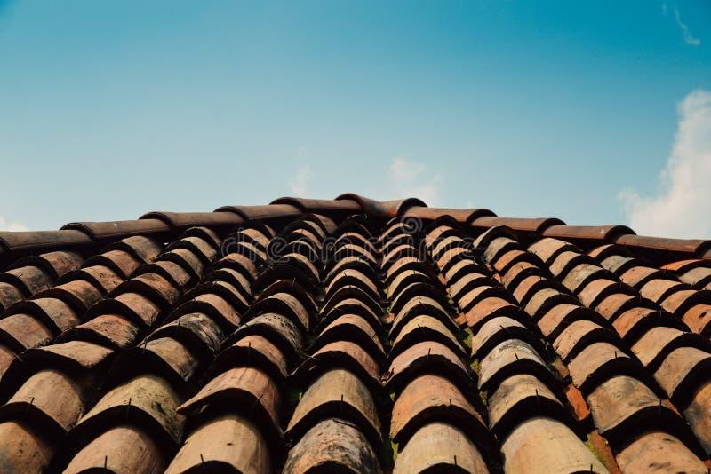 Diagonalni rzędy pomarańczowe gliniane dachowe płytki na Śródziemnomorskim miasteczku z niebieskie niebo kopii przestrzenią zdjęcia stock